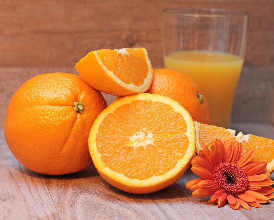 Des oranges à côté d'un verre de jus de fruit et une fleur